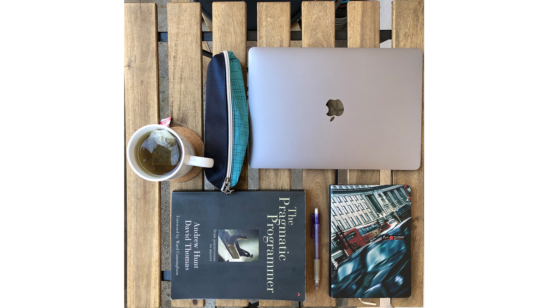 Reading technical books - macbook, notebook, cofffee and pens on a table